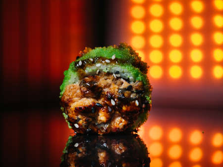 Baked sushi roll with green tobiko caviar lighted up with red led lights on reflective background Stok Fotoğraf