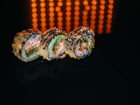 Tempura sushi roll with snow crab lighted up with red led lights on reflective background