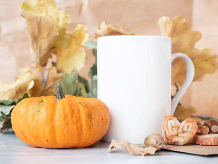 Tea cup near decorative pumpkin on autumn background with dry oak leaves.