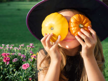 Portrait of girl in witch hat holding two decorative pumpkins in front of her face outdoors Zdjęcie Seryjne