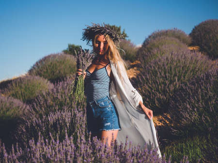 Carefree and happy young woman in jeans shorts enjoying life in purple lavender field