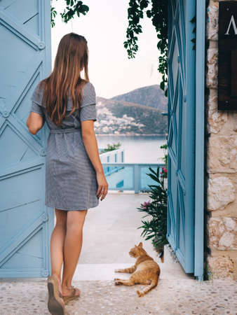 Young woman with cat standing near blue open door and looking at beautiful sea resort view. Backside view