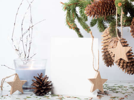 White empty paper on the table with christmas decor. Fir tree bouquet, candle and wooden star hangers on white background Zdjęcie Seryjne
