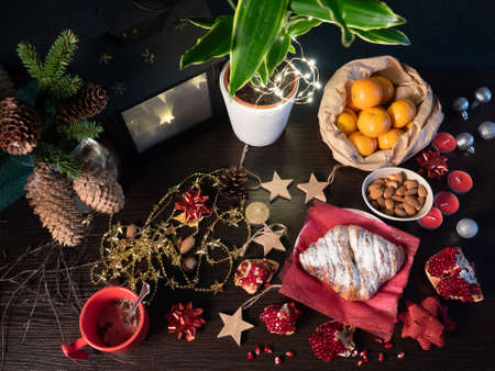 Cozy winter evening table with bun, hot chocolate, almonds, tangerines and Christmas decorations