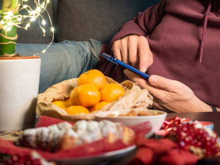 Closeup view of man with cellphone sitting in the living room near Christmas decorated table