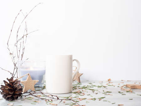 White ceramic mug on the table with christmas decor. Birch tree bouquet, candle and wooden star hangers on white background Zdjęcie Seryjne