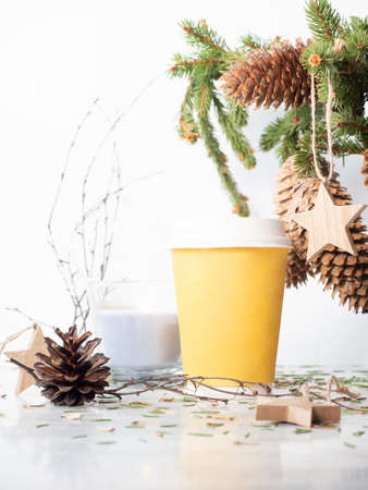 Take away cardboard cup on the table with christmas decor. Fir tree bouquet, candle and wooden star hangers on white background