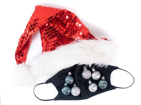 Black face mask decorated with christmas ornament with red Santa hat on white background