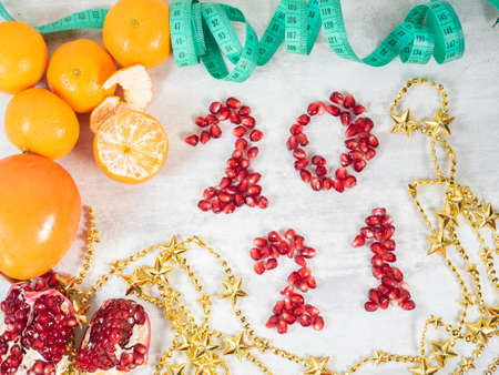 2021 number made from pomegranate seeds, fruits and tape measure on the table . Healthy eating concept