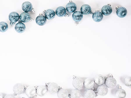 Christmas background. Frame of glitter blue and silver Christmas balls on white background. Flat lay, top view.