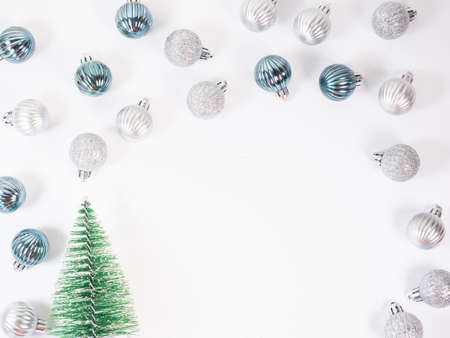 Christmas background. Glitter blue and silver Christmas balls around small fir tree toy on white background. Flat lay, top view.