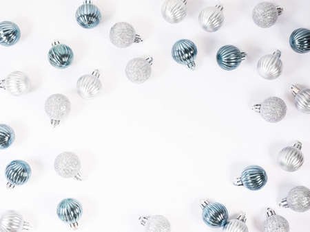 Christmas background. Glitter blue and silver Christmas balls on white background. Flat lay, top view.