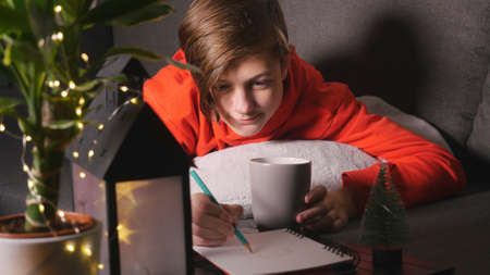 Cute boy with cup lying on the sofa and drawing picture. Evening time christmas lights and decorations