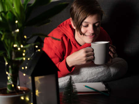Cute boy with cup lying on the sofa. Evening time christmas lights and decorations