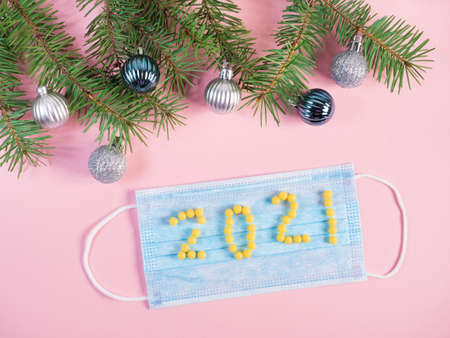 Happy new year 2021 of yellow pills on blue medical mask on pink background with christmas decorations