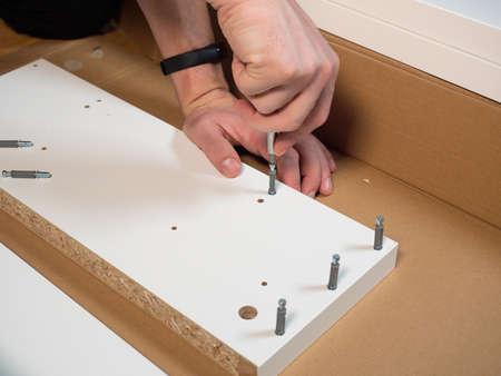 Mans hand driving screw into wooden cupboard shelf.