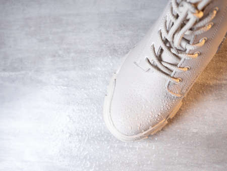 Closeup view of water droplets on white color winter shoe protected with waterproof spray