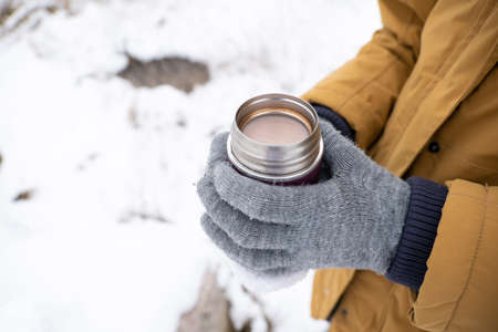 The unrecognizable person holding a small flask with hot chocolate outdoors snowy wintertime