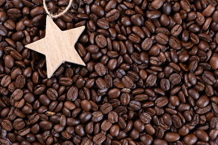 Closeup high angle view of wooden star lying on coffee beans background