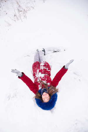Young funny woman in red coat lying on the snow. Enjoying winter time