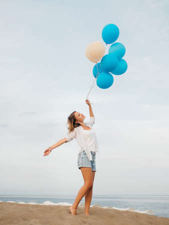 Young happy woman holding blue and white helium balloons standing on the sandy beach near the sea in cloudy weather 写真素材