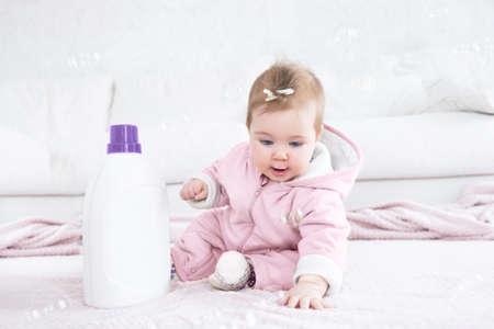 Adorable baby girl sitting on the floor near cloth washing gel