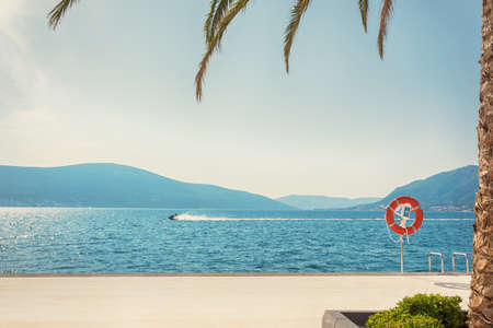 Lifesaving Buoy by the sea coast  and silhouettes of people in motion on jetski on the luxury holiday