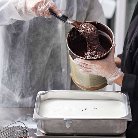 Women hands in gloves preparing chocolate ice cream - pouring chocolate ganache in stainless steel tray
