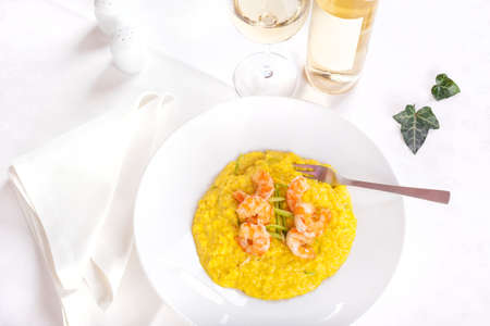 Sunlit plate of king prawns with saffron rice and zucchini - Paella Valenciana served with white wine 写真素材