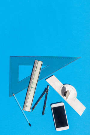 Geometry set with compass, rulers, pencil and protractor on blue background - top view