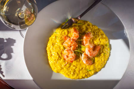 Sunlit plate of king prawns with saffron rice and zucchini - Paella Valenciana served with glass of white wine - top view 写真素材