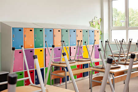 Close up of modern empty classroom with colorful lockers and raised chairs on the tables - back to school