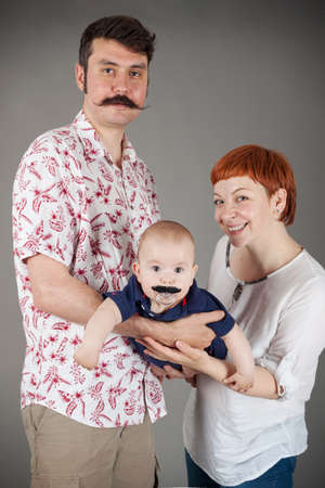 Happy Family- Fun family portrait, father with real Handlebar mustache, son with fake mustaches on his pacifier and a smiling Mother,vertical, studio isolated on grey with vignette Standard-Bild