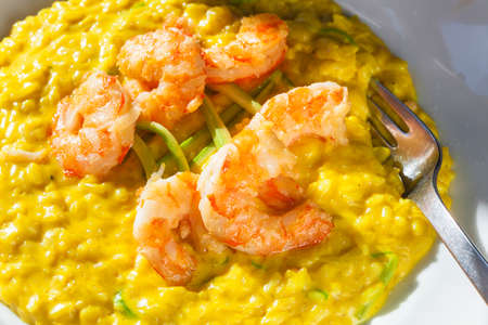Sunlit plate of king prawns with saffron rice and zucchini - Paella Valenciana - macro photography 写真素材
