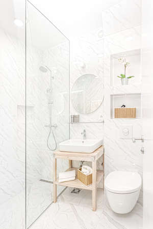 Bright new bathroom interior with glass walk in shower with marble tile surround 写真素材