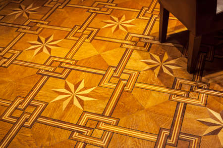 Vintage ornament. Decorative pattern parquet floor with part of emty chair in corner 写真素材