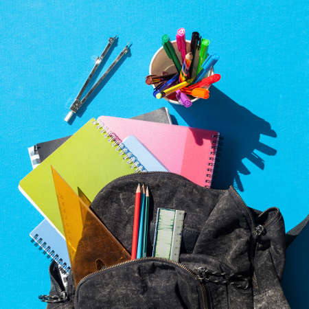 Square format of an overview of a schoolbag contents, blue background Foto de archivo