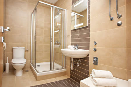 Bright new bathroom interior with glass walk in shower with cream color tile surround 写真素材