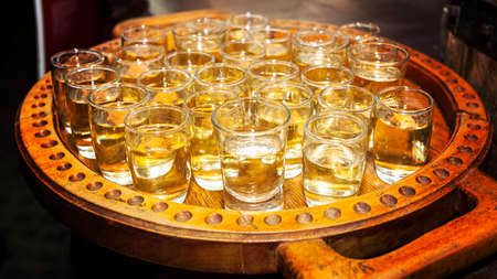 Traditional serbian brandy called rakija - small glasses filled with fruit brandy on a wooden tray