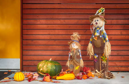 Halloween straw dolls, pumpkins, jack-o-lantern and leaves on wooden background
