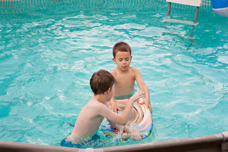 Happy kids playing in the swimming pool. Having fun in water pool outside on summer day. Leisure and swimming at holidays. Happiness and joy.