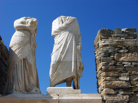 Stone headless statues of man and women in island Delos near the Mykonos,Greece photo