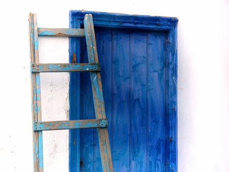 Blue ladder leaning against the blue door photo
