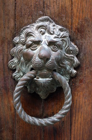 Traditional Venetian gilded lion head door knob in Venice on the wooden door photo
