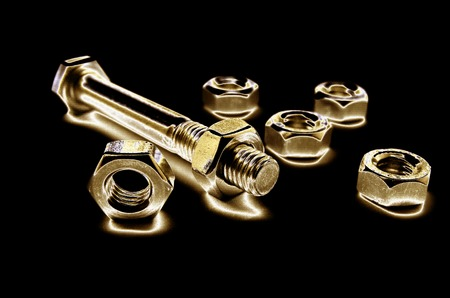 Golden Screws And Bolts Isolated On Black Background photo