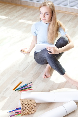 young teenage girl on the floor thinking and drawing photo