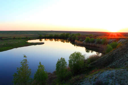 landscape lake in steppe on sundown by springtime