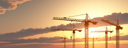 Construction cranes at sunset Imagens