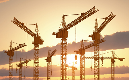 Construction cranes at sunset Stock Photo