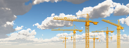 Construction cranes against a blue sky with clouds